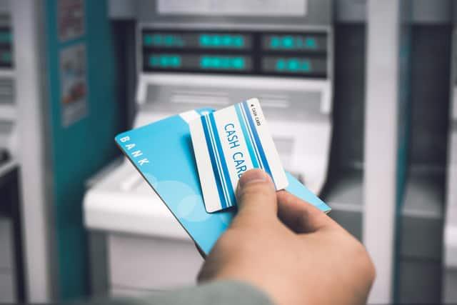 キャッシュカードと通帳を持つ手