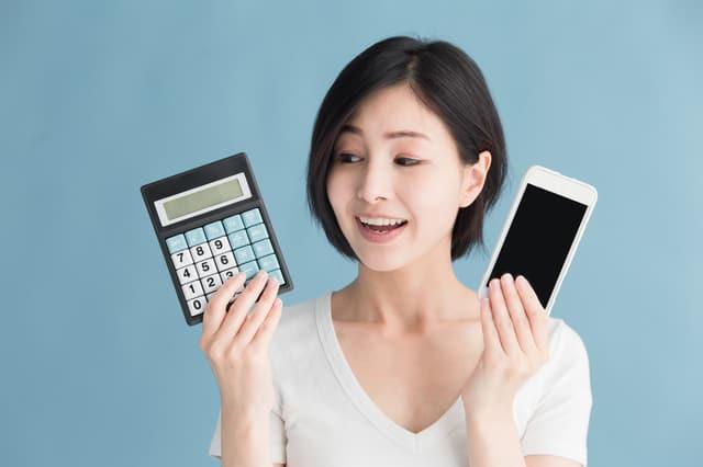 電卓とスマホを持つ女性