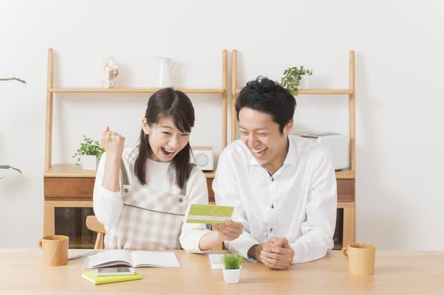 通帳を見て喜ぶ夫婦