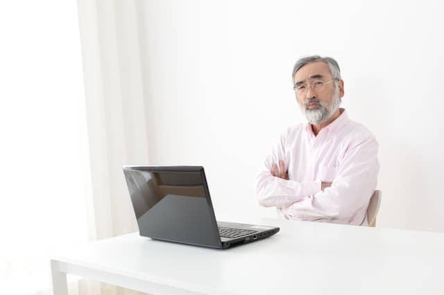 パソコンを前に悩むシニア男性