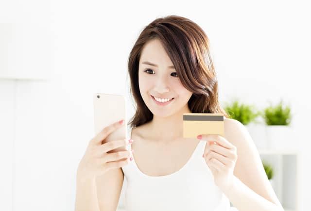 カードとスマホを持つ女性