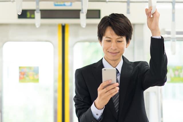 電車でスマホを操作するサラリーマン