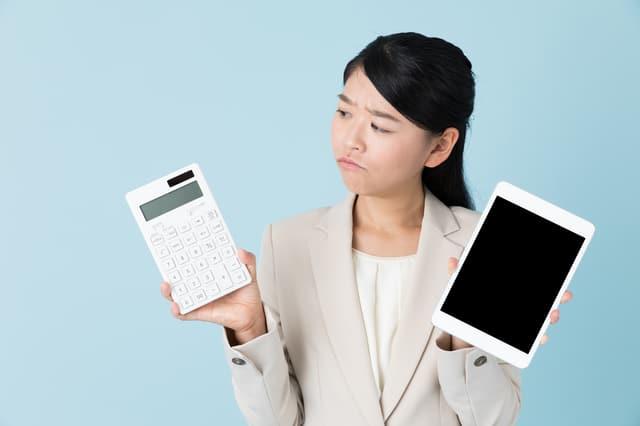 タブレットと電卓を持つ女性
