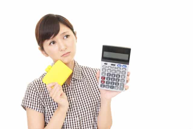 電卓と財布を持つ女性
